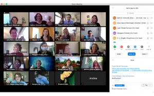 Screenshot of a Zoom meeting. Attendees are raising various glasses and bottles in a toast.